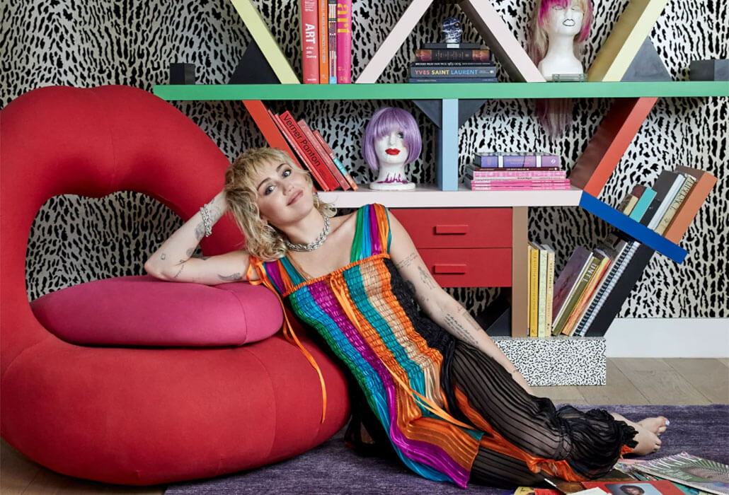 miley cyrus leaning on a red lips cushion wearing a colourful jumpsuit