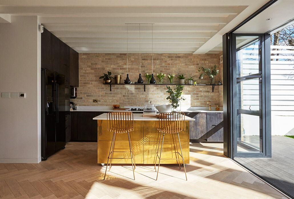 image of tash south's kitchen featuring a brass kitchen island with Rockett st george midas bar stools