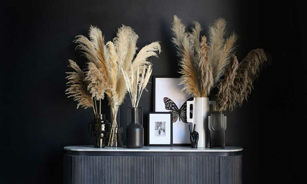 image of a mix of tall stem vases for pampas grass styled with quirky peace hands and artwork.