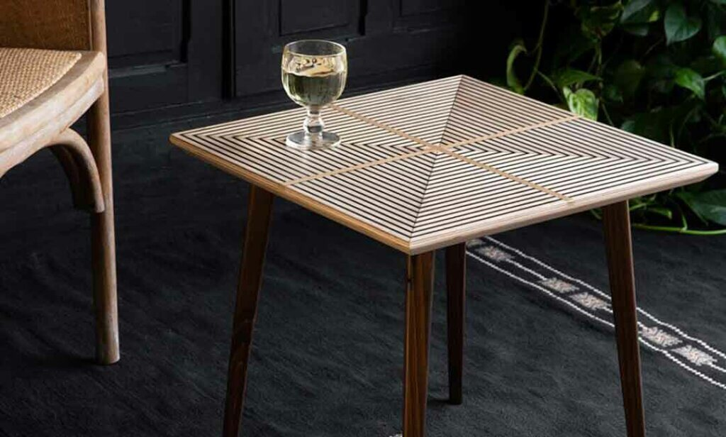 image of the Square Sustainable Side Table with a goblet of water sat on top of the table.